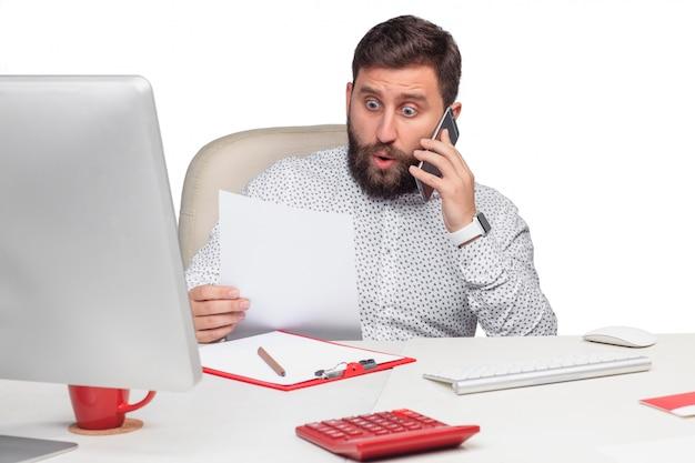 Retrato do empresário falando no celular no escritório Foto gratuita