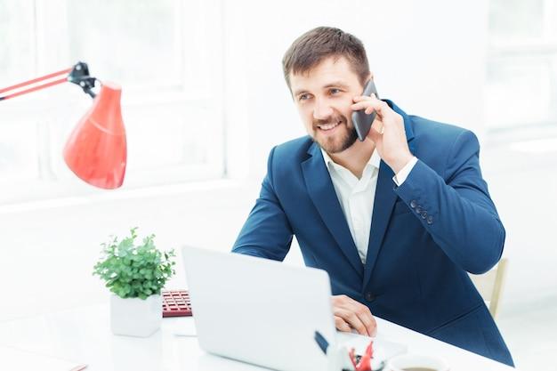 Retrato do empresário falando no telefone no escritório Foto gratuita