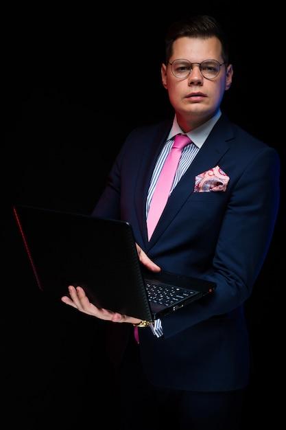 Retrato do empresário sério bonito confiante, trabalhando no laptop isolado no preto Foto Premium