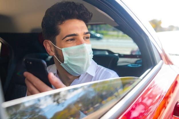 Retrato do empresário usando máscara facial e usando seu telefone celular a caminho do trabalho em um carro. conceito de negócios. novo conceito de estilo de vida normal. Foto gratuita