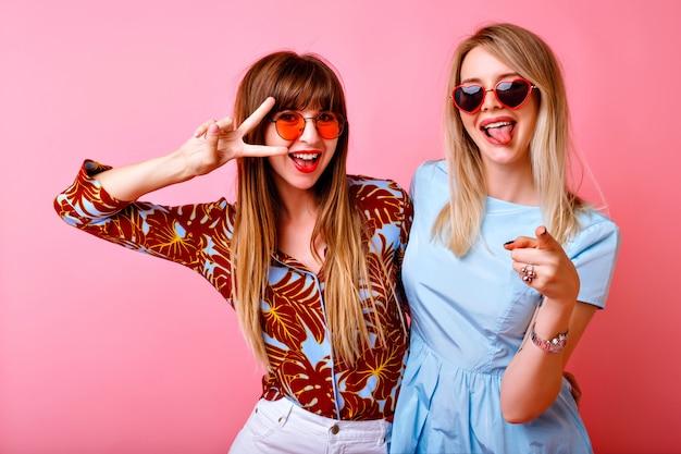 Retrato do estilo de vida de felizes lindas garotas de irmã de dois melhores amigos, posando e se divertindo juntos na parede rosa, mostrando língua comprida ev gesto, clima de festa positivo. Foto gratuita