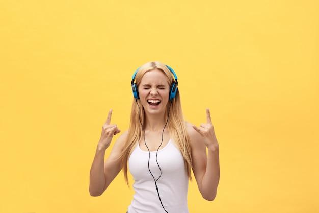Retrato do estilo de vida de uma mulher feliz ouvindo música em fones de ouvido isolado em um fundo amarelo Foto Premium