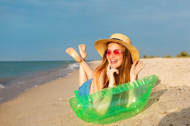 Retrato do estilo de vida de uma mulher loira de beleza feliz deitada no colchão de ar tomando banho de sol na praia, sorrindo e aproveitando as férias de verão Foto gratuita