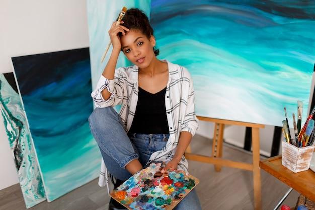 Retrato do estilo de vida do jovem estudante africano sentado com incrível arte abstrata mar acrílico mão desenhada obras de arte no estúdio. Foto gratuita