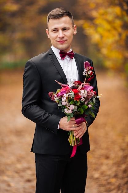 Retrato do estilo de vida do noivo feliz que levanta para a câmera ao ar livre na natureza com o carvalho no fundo. noivo alegre com cara sorridente no jakcet, gravata borboleta e retrato de camisa branca Foto Premium