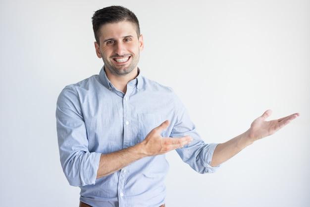 Retrato do gerente caucasiano novo alegre que mostra o produto. Foto gratuita