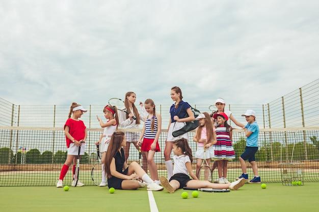 Retrato do grupo de meninas e menino como jogadores de tênis que mantêm raquetes de tênis contra a grama verde da corte ao ar livre. Foto gratuita