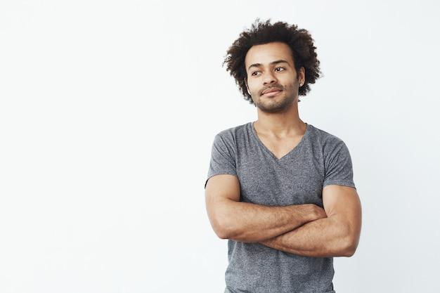 Retrato do homem africano stong e bonito que olha o levantamento esquerdo com os braços cruzados sobre a parede branca. conceito de inicialização confiante. Foto gratuita