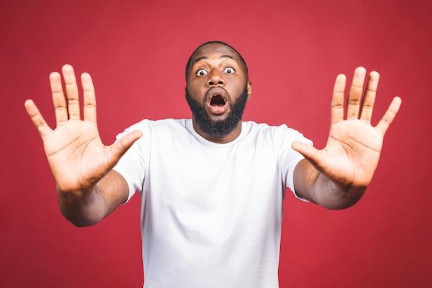 Retrato do homem afro-americano que guarda a mão no sinal de stop, advertindo e impedindo-o de algo ruim, olhando a câmera com expressão preocupada. Foto Premium