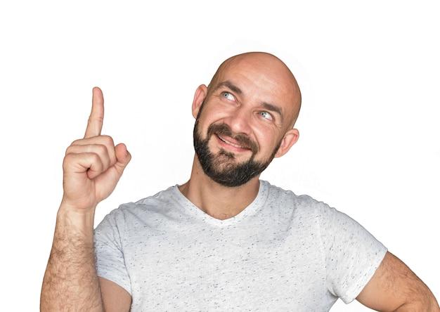 Retrato do homem calvo branco com a barba no t-shirt branco que sorri e que mostra o polegar acima. isolar-se sobre um fundo branco Foto Premium