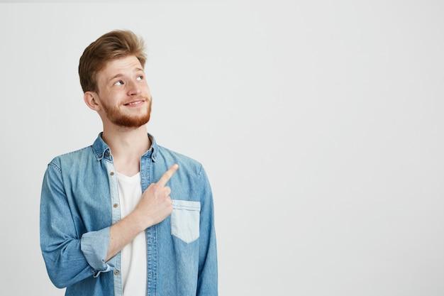 Retrato do homem considerável novo alegre que sorri apontando o dedo acima. Foto gratuita