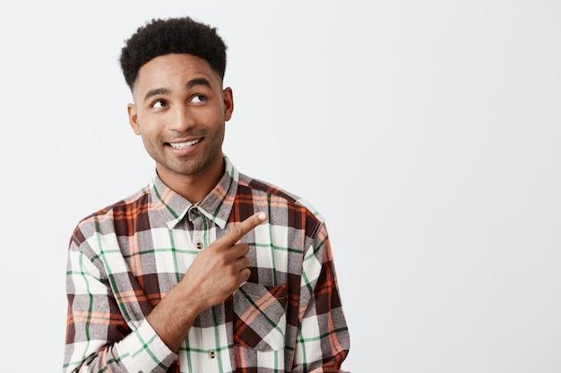 Retrato do homem de pele negra atrativo maduro feliz alegre com penteado afro na camisa quadriculado ocasional que olha de lado com sobrancelhas levantadas e sorriso, apontando com mão na parede branca. Foto gratuita
