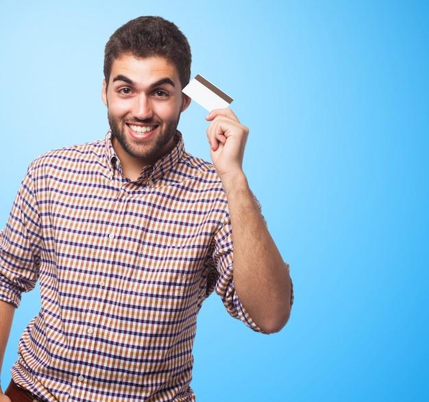 Retrato do homem que mostra o cartão de plástico. Foto gratuita