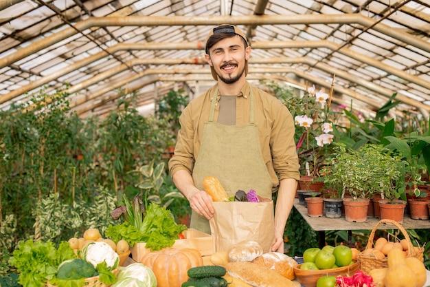 Retrato do jovem agricultor barbudo sorridente de boné e avental em pé no balcão com vários produtos e embalando legumes frescos em um saco de papel Foto Premium