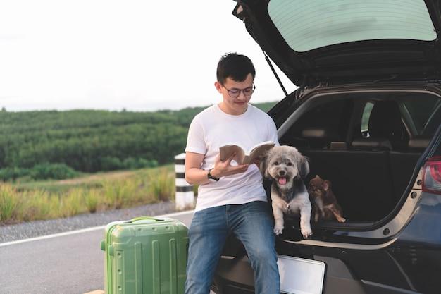 Retrato do livro de leitura asiático novo do homem ao sentar-se no tronco aberto do carro com seus cães. Foto Premium