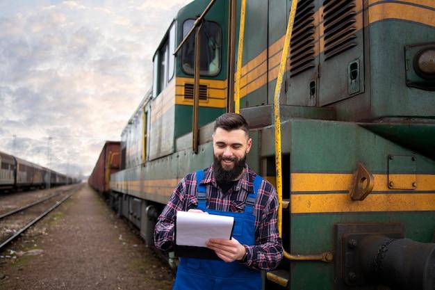 Retrato do maquinista ao lado da locomotiva na estação de trem e segurando o horário de partida Foto gratuita