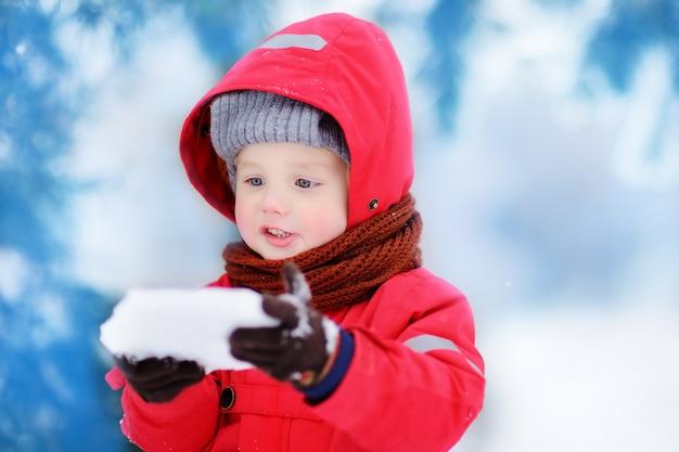 Retrato do menino engraçado pequeno na roupa vermelha do inverno que tem o divertimento com parte de gelo. lazer ativo ao ar livre com crianças no inverno. garoto com chapéu quente, luvas de mão e cachecol Foto Premium