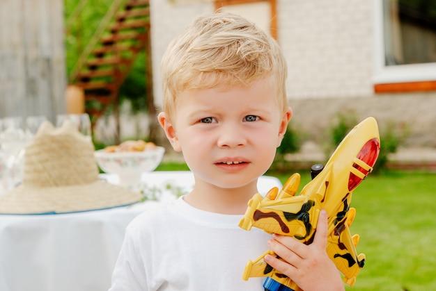 Retrato do menino louro pequeno feliz bonito que guarda brinquedos do plano e do carro. adorável criança andando no parque em dia ensolarado. Foto Premium