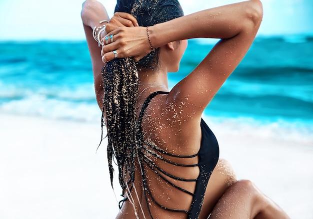 Retrato do modelo bonito caucasiano mulher bronzeada com cabelos longos escuros no maiô preto posando na praia de verão com areia branca no céu azul e oceano Foto gratuita