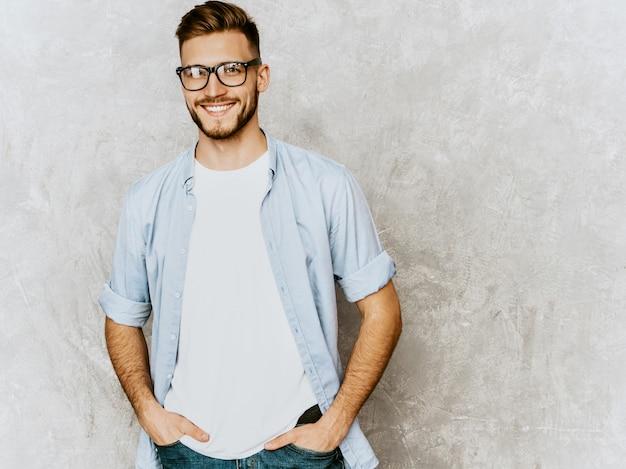 Retrato do modelo bonito jovem sorridente, vestindo roupas de camisa casual. homem elegante moda posando em espetáculos Foto gratuita