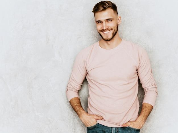 Retrato do modelo bonito jovem sorridente, vestindo roupas de verão casual rosa. moda elegante homem posando Foto gratuita