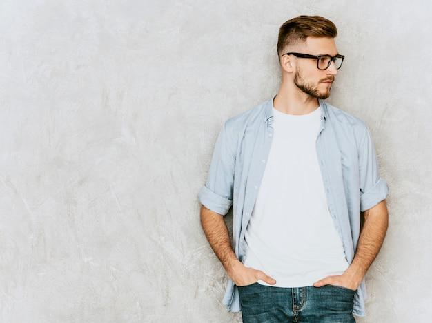 Retrato do modelo bonito sério jovem vestindo roupas de camisa casual. homem elegante moda posando em espetáculos Foto gratuita