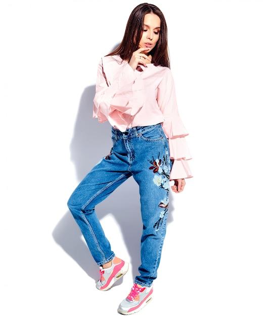 Retrato do modelo caucasiano sorridente mulher morena bonita blusa rosa brilhante e verão azul elegante jeans com flores imprimir Foto gratuita