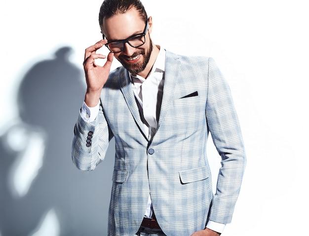 Retrato do modelo de empresário de moda hipster elegante bonito vestido elegante terno azul claro em copos em branco. Foto gratuita