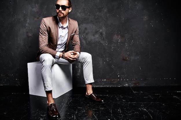 Retrato do modelo de empresário de moda hipster elegante bonito vestido elegante terno marrom sentado perto escuro Foto gratuita