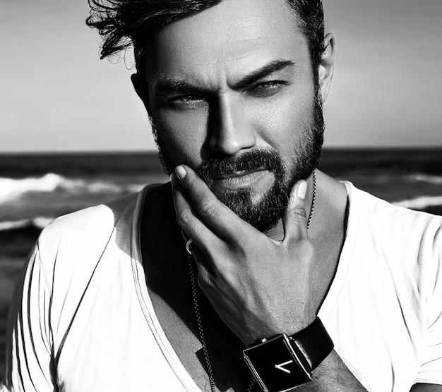 Retrato do modelo de homem bonito moda vestindo roupas brancas, posando no mar azul Foto gratuita