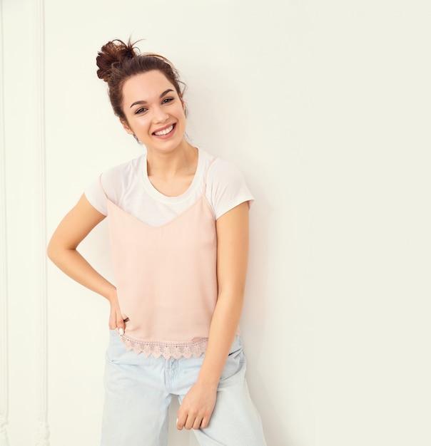 Retrato do modelo de menina jovem morena linda com maquiagem nude em roupas de verão colorido rosa hipster posando perto da parede. olhando feliz Foto gratuita