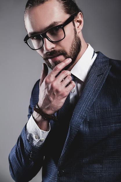 Retrato do modelo de moda bonito empresário vestido elegante terno azul com óculos Foto gratuita