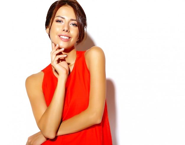 Retrato do modelo de moda jovem bonito em um vestido vermelho em uma parede branca Foto gratuita