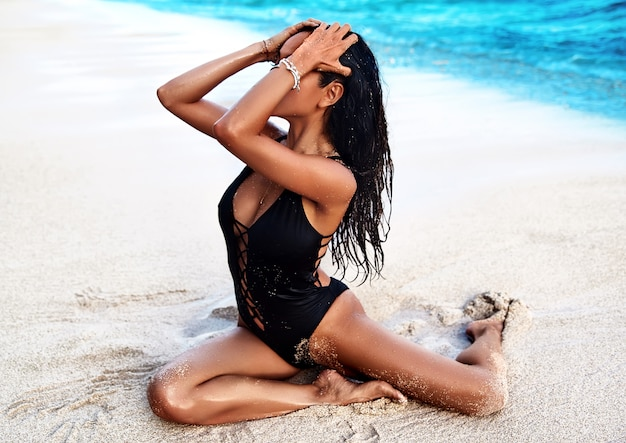 Retrato do modelo de mulher bonita banhos de sol caucasiano com cabelos longos escuros em maiô preto, posando na praia de verão com areia branca na parede do céu azul e oceano. tocando seu cabelo Foto gratuita