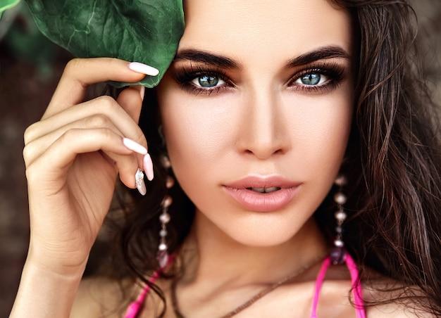 Retrato do modelo de mulher bonita caucasiano com cabelos longos escuros no maiô rosa tocando folha tropical verde Foto gratuita