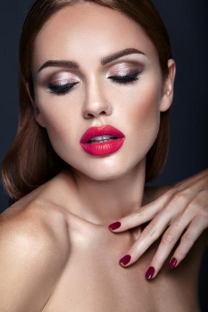Retrato do modelo de mulher bonita com maquiagem de noite e penteado romântico. lábios vermelhos Foto gratuita
