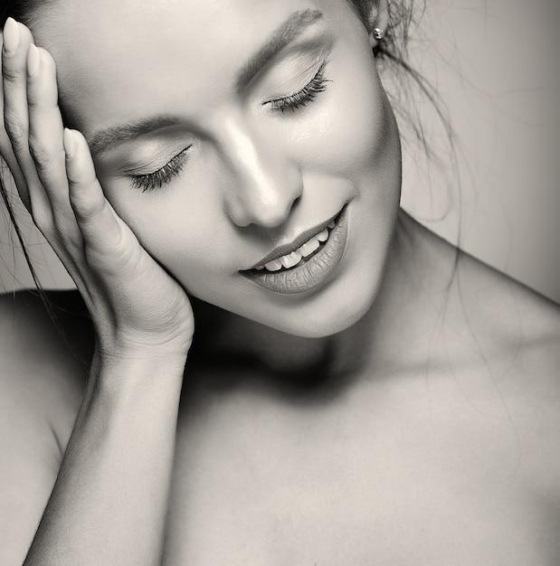 Retrato do modelo de mulher bonita com maquiagem diária fresca e lábios vermelhos, tocando a cabeça Foto gratuita