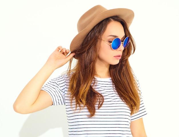 Retrato do modelo de mulher jovem rindo elegante em roupas de verão casual com chapéu marrom isolado na parede branca Foto gratuita