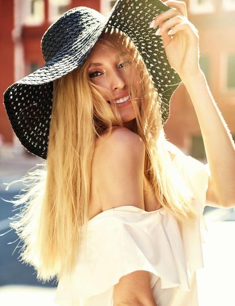 Retrato do modelo de mulher loira sensual, vestido de vestido branco e chapéu de praia verão posando no fundo da rua atrás do pôr do sol Foto gratuita
