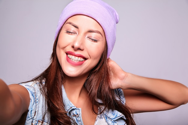 Retrato do modelo de mulher morena bonita sorridente bonito em roupas de jeans casual verão sem maquiagem no gorro roxo, fazendo foto de selfie telefone isolado no cinza Foto gratuita