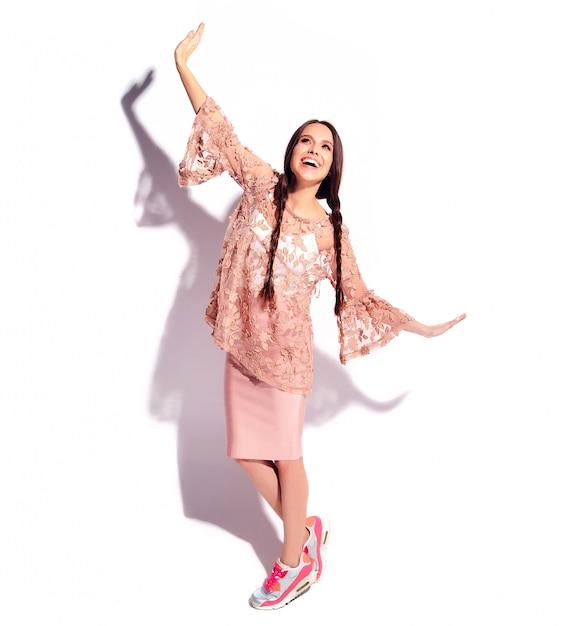 Retrato do modelo de mulher morena sorridente caucasiano bonito com tranças duplas em roupas elegantes de verão rosa brilhante Foto gratuita