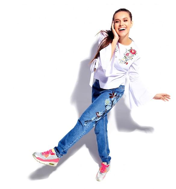Retrato do modelo de mulher morena sorridente caucasiano bonito na blusa branca e calça jeans azul elegante de verão com flores Foto gratuita