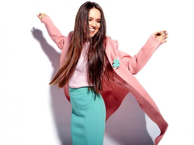 Retrato do modelo de mulher morena sorridente caucasiano bonito no sobretudo rosa brilhante e saia azul elegante de verão isolada no fundo branco Foto gratuita