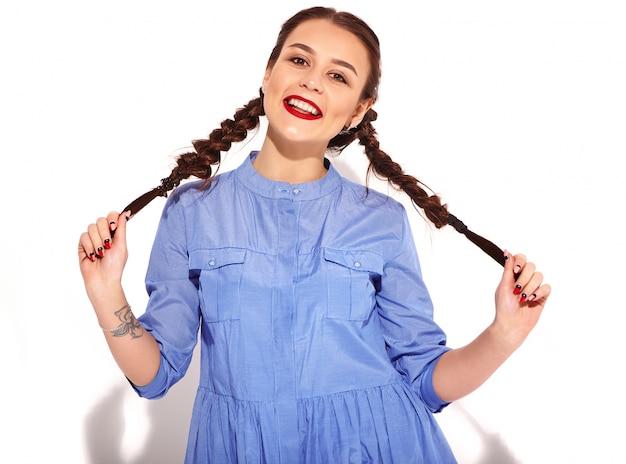 Retrato do modelo de mulher sorridente feliz jovem com maquiagem brilhante e lábios vermelhos com duas tranças nas mãos no vestido azul colorido de verão isolado Foto gratuita