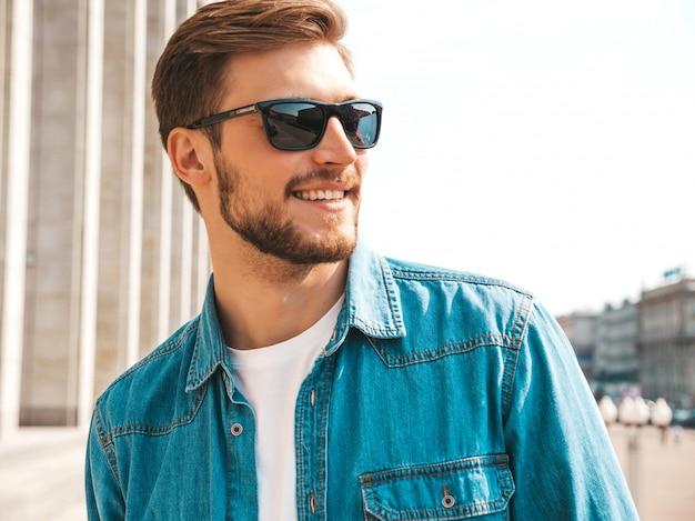 Retrato do modelo de sorriso bonito do homem de negócios lumbersexual do moderno à moda. homem vestido com roupas de jaqueta jeans. Foto gratuita
