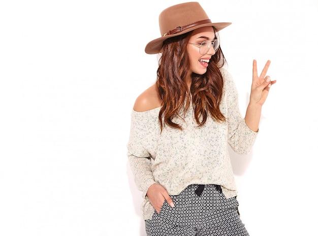 Retrato do modelo elegante jovem em roupas de verão casual no chapéu marrom com maquiagem natural em copos isolados. e mostrando sinal de paz Foto gratuita