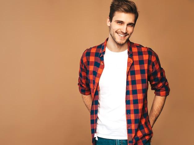Retrato do modelo elegante jovem sorridente bonito vestido com camisa quadriculada vermelha. homem moda, posar Foto gratuita