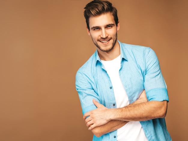 Retrato do modelo elegante jovem sorridente bonito vestido com roupas de camisa azul. homem moda posando. braços cruzados Foto gratuita