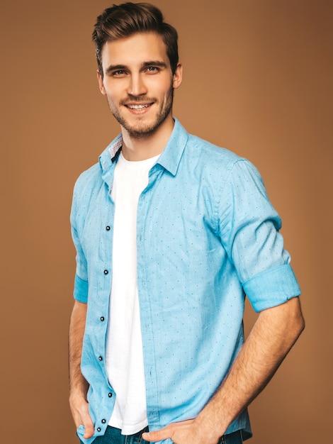 Retrato do modelo elegante jovem sorridente bonito vestido com roupas de camisa azul. homem moda, posar Foto gratuita