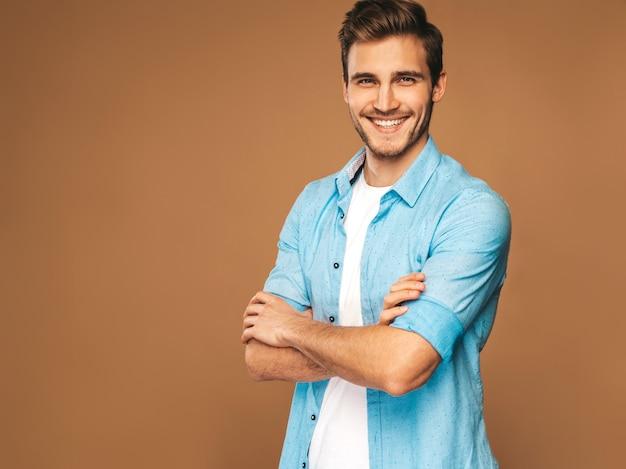 Retrato do modelo elegante jovem sorridente bonito vestido com roupas jeans. homem da moda. posando Foto gratuita
